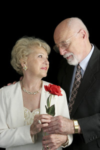A handsome senior couple in love.  He's giving her a rose.  A hearing aid is visible in her ear.